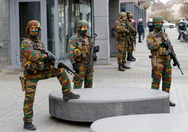 Soldiers stand guard as they take position in the Brussels district of Molenbeek. Belgium charged four...
