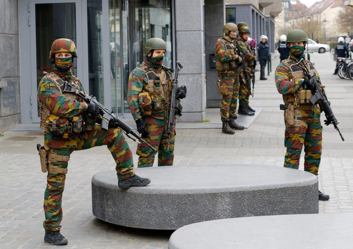 Soldiers stand guard as they take position in the Brussels district of Molenbeek. Belgium charged four people with being part
