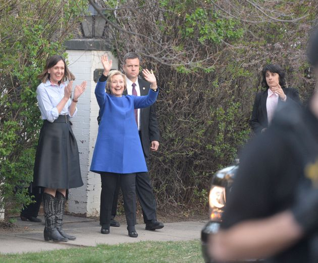 Hillary Clinton waves to neighbors as she leaves a fundraising party at Colorado Governor John Hickenlooper's
