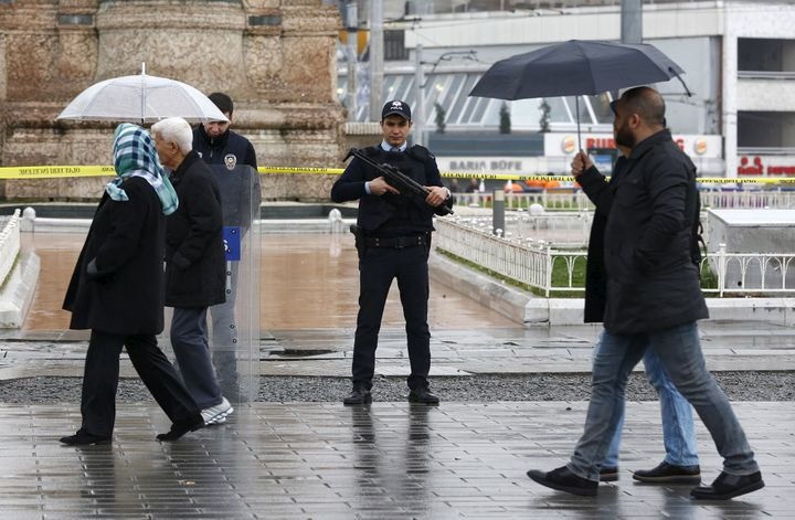 Police officers stand guard at Taksim square after a suicide bombing on a major shopping and tourist district in central Ista