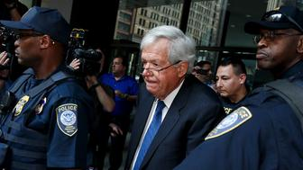 Former U.S. House of Representatives Speaker Dennis Hastert is surrounded by officers as he leaves federal court after pleading not guilty to federal charges of trying to hide large cash transactions and lying to the FBI in Chicago, Illinois, United States, June 9, 2015. According to an indictment, Hastert, 73, was trying to evade detection of $3.5 million in payments he had promised to make to someone from his hometown of Yorkville, Illinois, to conceal past misconduct against the person. REUTERS/Jim Young