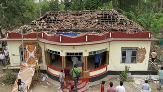 People gather around a damaged section of a temple after a fire broke out at a temple in Kollam in the southern state of Kerala, India, April 10, 2016. A huge fire swept through a temple in India's southern Kerala state early on Sunday (April 10), killing nearly 80 people and injuring over 200 gathered for a fireworks display to mark the start of the local Hindu new year. REUTERS/Sivaram V      TPX IMAGES OF THE DAY