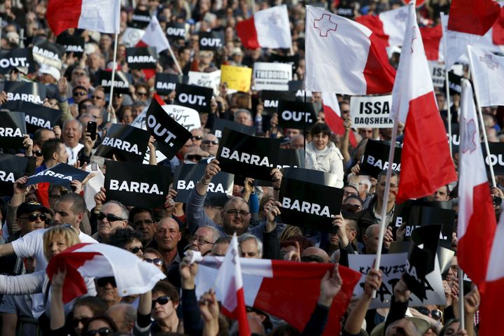 "Protestors hold posters reading ""Out"" during a demonstration calling on Maltese Prime Minister Joseph Muscat to resign after"