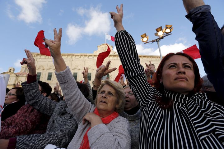 Protestors make victory signs during a demonstration calling on Maltese Prime Minister Joseph Muscat to resign.