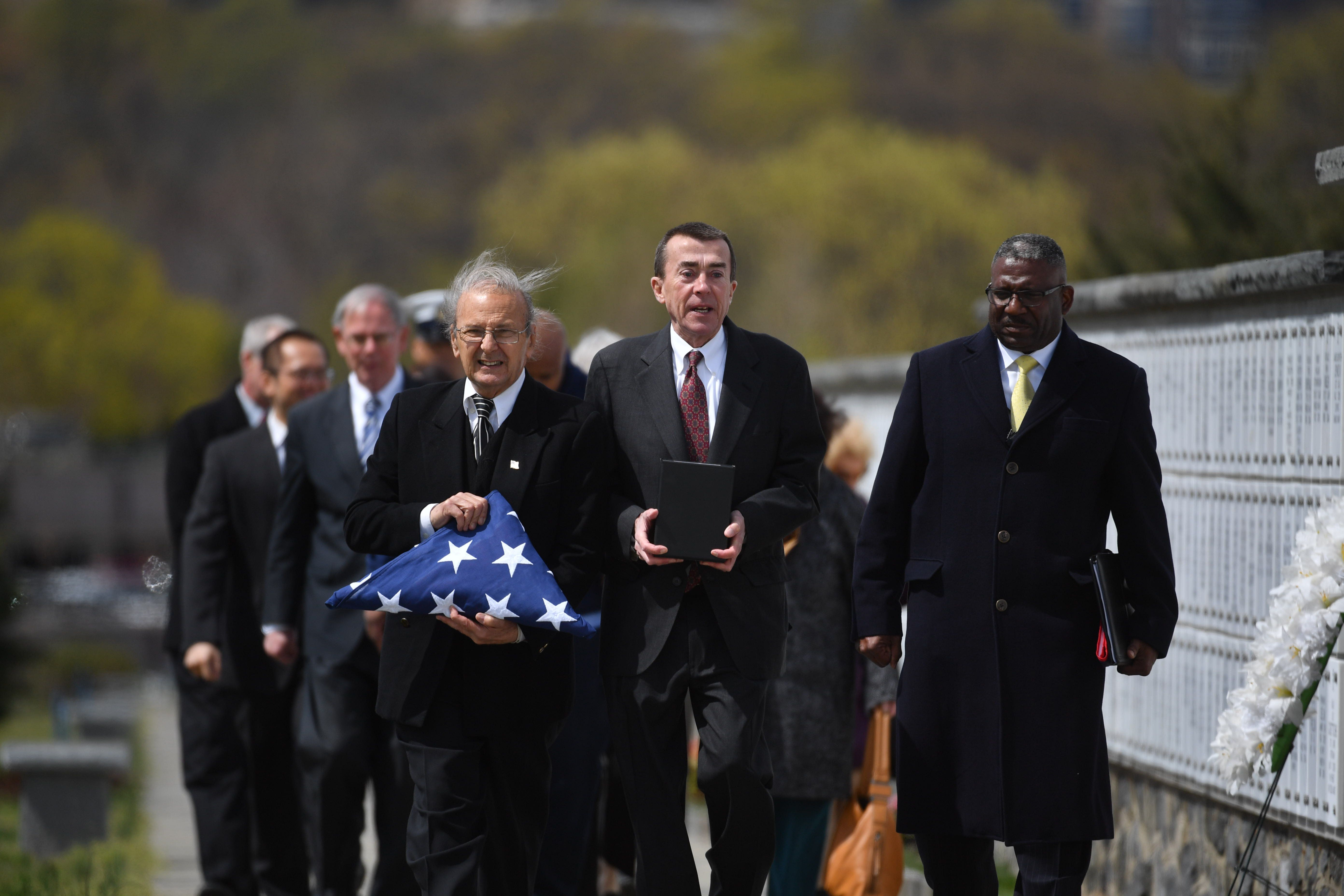 ARLINGTON, VA- APRIL 08: Nick Addams (left)  and and Bill Sheppard (center) attend the  memorial service for World War 2 veteran Andrew Moore at Arlington National Cemetery in Arlington, Virginia on April 08, 2016. ALSO PICTURED, Charles Moore, Arlington National Cemetery Representative (right)  World War II veteran Andrew Moore died alone in December and his neighbors banded together to get him placed at Arlington National Cemetery. Andrew Moore died at 89 in December was destined for a paupers grave. He grew up in an orphanage, never married and outlived his friends. But a couple of his neighbors in the State apartment building, where Moore lived for 40 years, wanted something better for him, so they worked the bureacracy and raised the money to have Moore's ashes placed at Arlington National Cemetery with a rifle salute. (Photo by Marvin Joseph/The Washington Post via Getty Images)