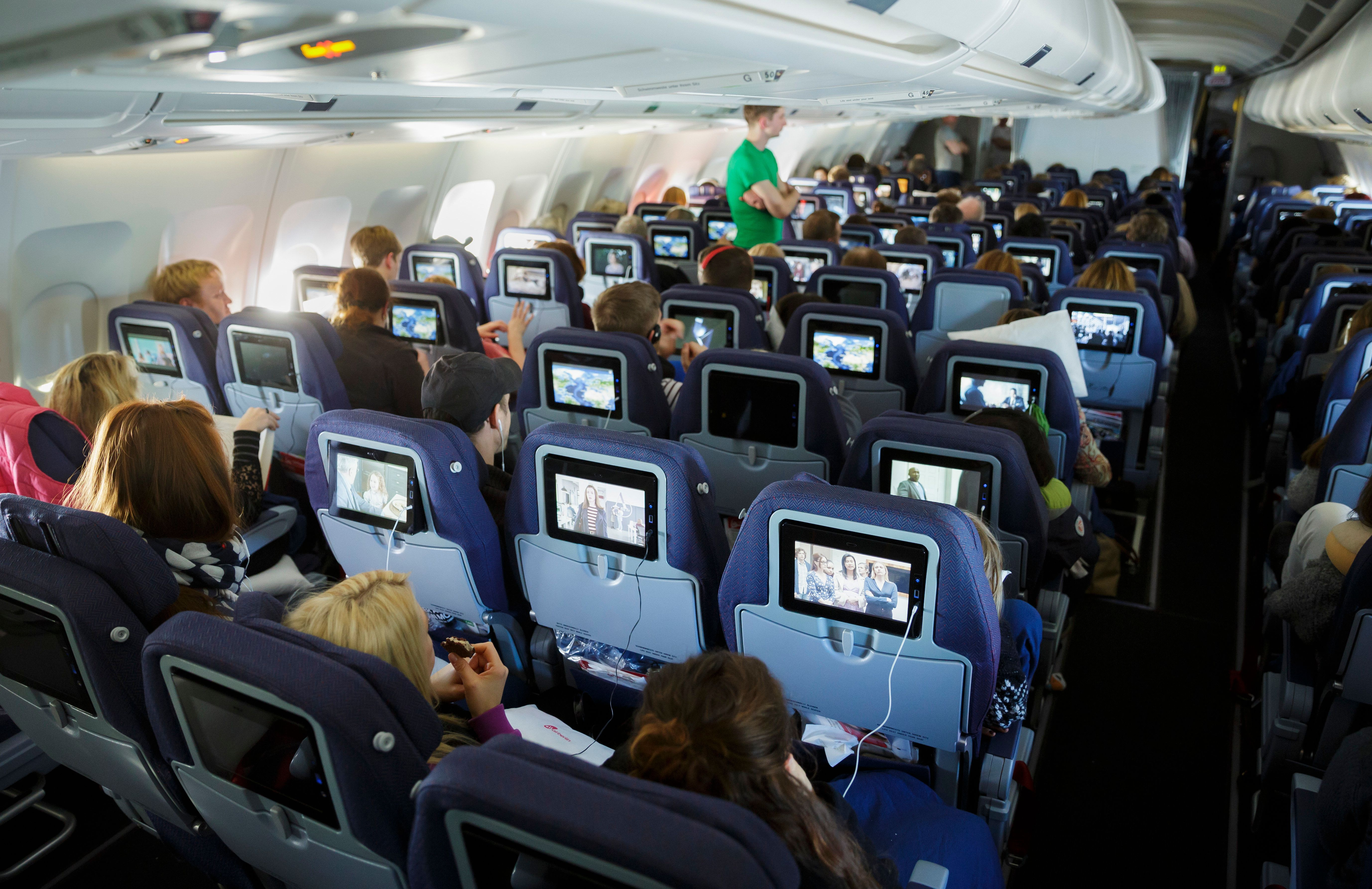 New York, United Sates of America - February 23: Passengers look at TV screens in Economy Class section in a plane on February 23, 2016 in Berlin, Germany. (Photo by Thomas Trutschel/Photothek via Getty Images)