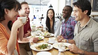 Happy Smiling Group Of Friends Meeting For Lunch In Coffee Shop