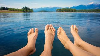 A couple's bare feet and legs as they relaxes while vacationing and resting on a beautiful mountain lake. Selective focus on the feet of the man and woman