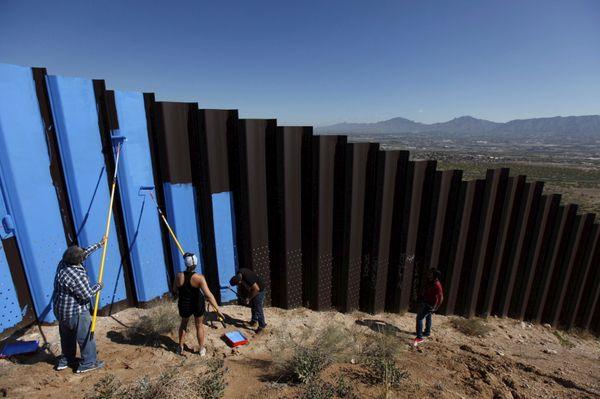 Ana Teresa Fernandez (in black) and Border/Arte members paint the fencein Ciudad Juárez.