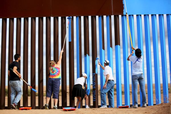 A group of volunteers painting the fence on Saturday.