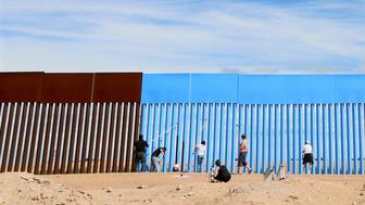 """Volunteers paint the border fence between the United States and Mexico to give the illusion of transparency during the """"Borrando la Frontera"""" (Erasing the Border) Art Project in Mexicali, Mexico April 9, 2016.  REUTERS/Sandy Huffaker    FOR EDITORIAL USE ONLY. NOT FOR SALE FOR MARKETING OR ADVERTISING CAMPAIGNS       TPX IMAGES OF THE DAY"""