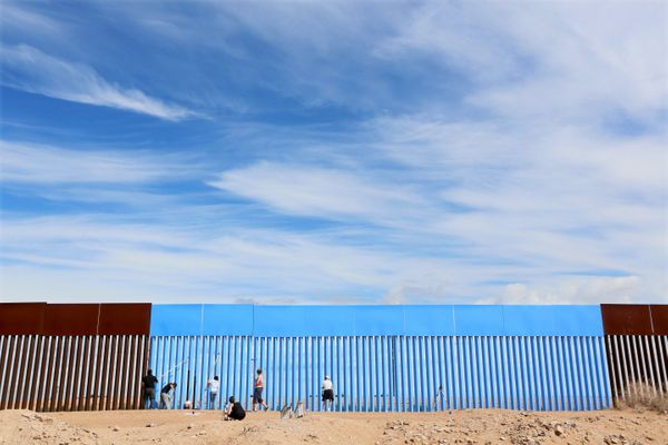 """Volunteers with the """"Borrando la Frontera"""" project in Mexicali paint the border fenceon Saturday."""