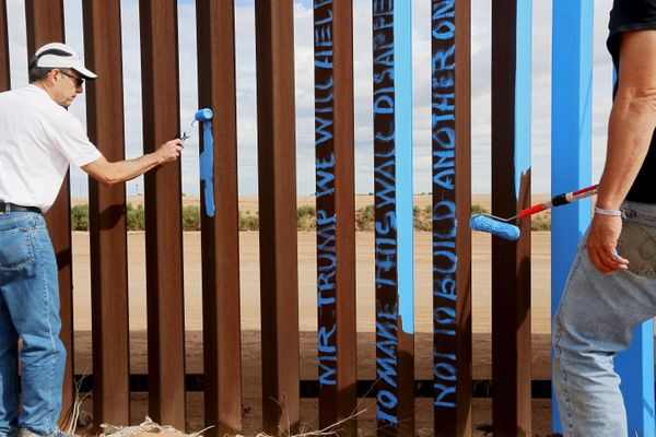Genaro Fernandez (left) and Dan Watman paint the fencesky blue to help give it the illusion of transparency.