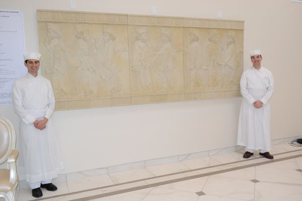 Two&nbsp;young <i>Mobeds,</i>&nbsp;or Priests, stand alongside a&nbsp;custom sculpted panel inspired by the ancient Tripylon