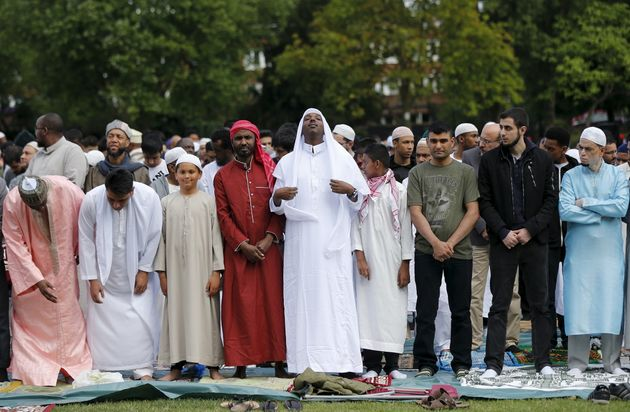 Muslim men prepare before a prayer service for Eid-al Fitr at a park in London in