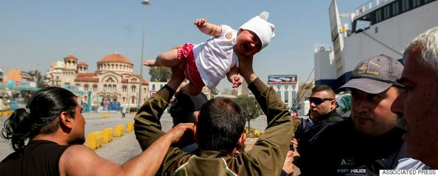 Photographers and journalists in Greece encountered an angry Afghan man lifting a baby over his head...