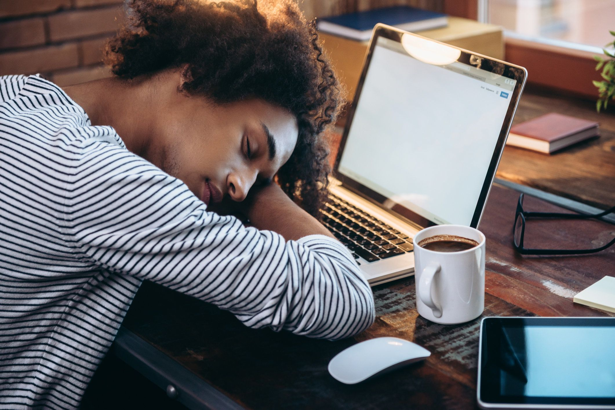 Side view of young African man sleeping on laptop with eyes closed while sitting at his working place