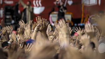People wave their hands in the air as TV host Stephen Colbert speaks on stage during the Global Citizen Festival in Central Park in New York, September 26, 2015. REUTERS/John Taggart