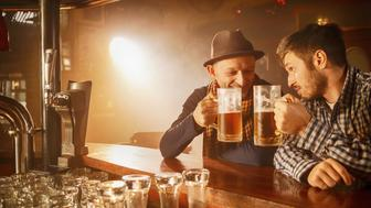Cheers. Two man  toasting and enjoying in beer on wooden counter at a bar. The grain and texture added. Very shallow DOF .