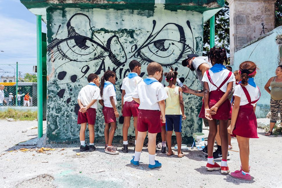 "Graffiti artist<a href=""https://www.instagram.com/abstrk/"">Abstrk</a>showing the children how to use spray paint"
