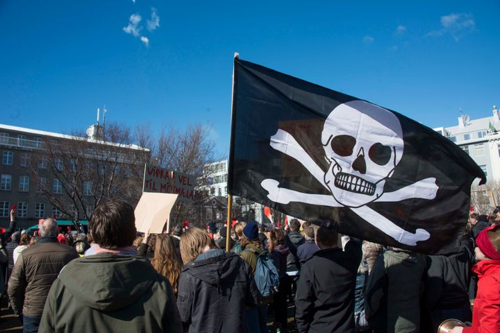 A pirate flag among thousands of Icelanders rallying in Reykjavik on April 9, 2016 to demand immediate elections on a sixth c