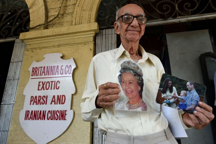 Kohinoor, 93, an ardent fan of the British royal family, poses with photos of Queen Elizabeth, and the duke and duchess of Ca
