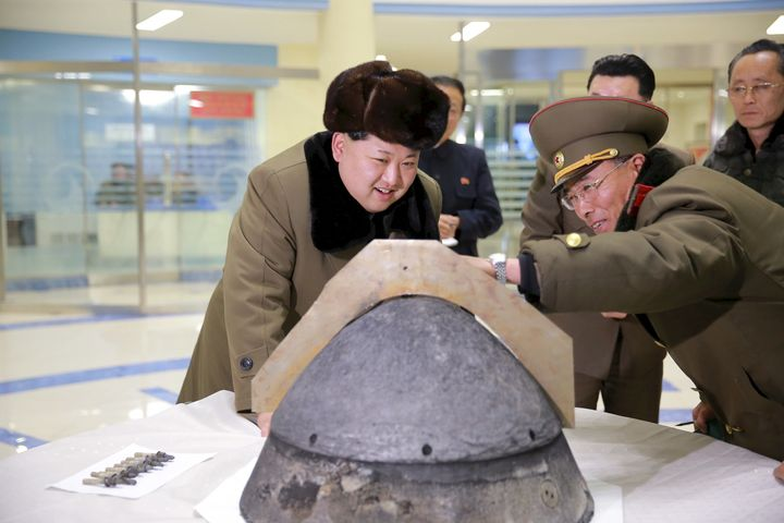 North Korean leader Kim Jong Un looks at a rocket warhead tip after a simulated test of atmospheric re-entry of a ballistic m