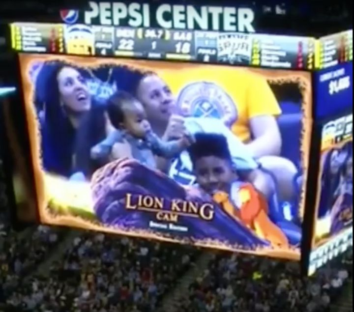 "A baby is seen being lifted up like Simba from Disney's ""Lion King"" movie during a Denver Nuggets basketball game."