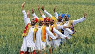 JAMMU, INDIA - APRIL 10: Artists perform the 'Bhangra', a punjabi folk dance, near India-Pakistan International border fence on the occasion of the Baisakhi festival in Suchetgarh organised by Border Security Force about 25 km from Jammu, on April 10, 2016 in Jammu, India. Baisakhi is the festival of the first harvest of the year right after the winter season in the north of India. (Photo by Nitin Kanotra/Hindustan Times via Getty Images)