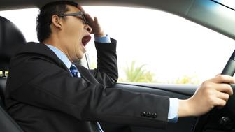 Asian Exhausted driver yawning and driving  car