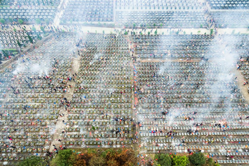 "People burn paper money as they pray at a cemetery in Fuzhou, Jiangxi province during <a href=""http://www.chinahighlights.com"