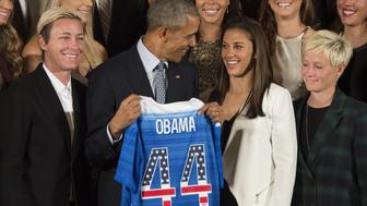 The US 2015 Women's World Cup Team's Abby Wambach (L) and Carli Lloyd (2nd R) present US President Barack Obama (C) with a team jersey during an event honoring them at the White House in Washington, DC, October 27, 2015.    AFP PHOTO / JIM WATSON        (Photo credit should read JIM WATSON/AFP/Getty Images)
