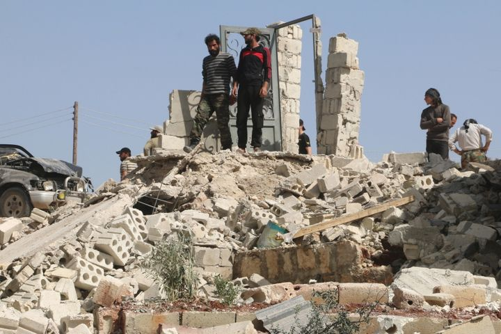 The Syrian conflict has killed over 250,000 and created millions of refugees. Men inspect damage after an airstrike in the op