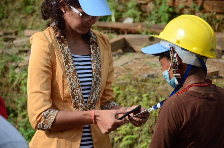 Hotrika Joshi, a UNDP volunteer, records the data card of a woman working to remove debris from her destroyed