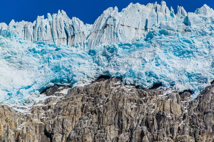 Massive walls of ice tower above a rock cliff on the edge of the Harding icefield. The couple reportedly hired a private plan