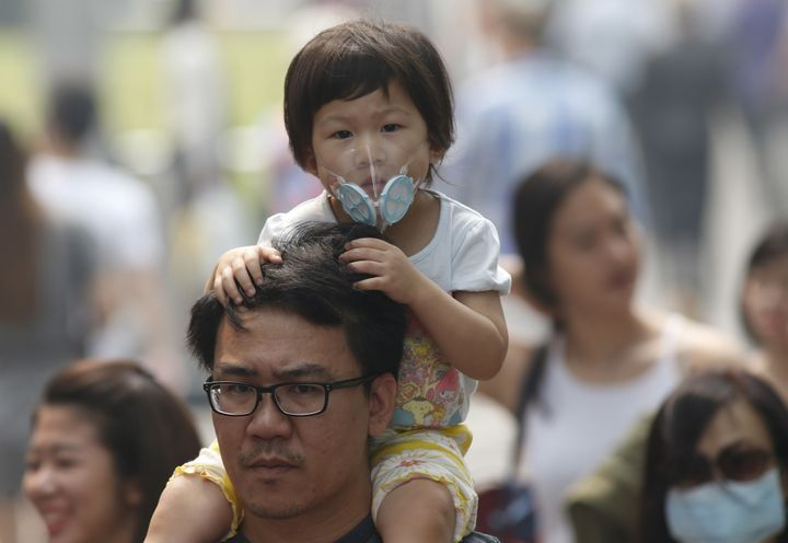 A man carries her daughter wearing a mask as they cross a road at the haze-shrouded shopping district of Orchard Road in Singapore September 24, 2015.