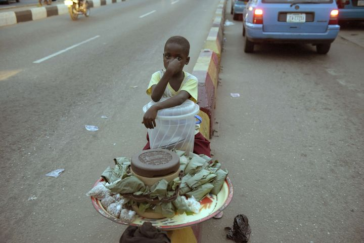 A child sits along the road at night to sell his wares in Nigeria. Many children in the north have little choice, with s