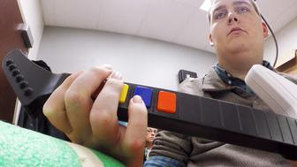 Ian Burkhart, 24, plays a guitar video game as part of a study with neural bypass technology in this undated handout picture released by Ohio State University Wexner Medical Center in Columbus, Ohio. Burkhart, who became paralysed in an accident, can now move his hands thanks to a computer chip in his brain that lets his mind guide his hands and fingers, bypassing his damaged spinal cord.   REUTERS/The Ohio State University Wexner Medical Center/Battelle/Handout via Reuters       ATTENTION EDITORS - THIS PICTURE WAS PROVIDED BY A THIRD PARTY. REUTERS IS UNABLE TO INDEPENDENTLY VERIFY THE AUTHENTICITY, CONTENT, LOCATION OR DATE OF THIS IMAGE. EDITORIAL USE ONLY. NOT FOR SALE FOR MARKETING OR ADVERTISING CAMPAIGNS. NO RESALES. NO ARCHIVE. THIS PICTURE IS DISTRIBUTED EXACTLY AS RECEIVED BY REUTERS, AS A SERVICE TO CLIENTS