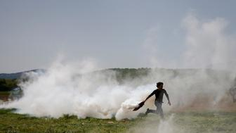 A migrant runs to throw back a tear gas canister during scuffles with police at a makeshift camp for refugees and migrants at the Greek-Macedonian border near the village of Idomeni, Greece, April 13, 2016. Macedonian police fired tear gas on Wednesday to disperse around 50 migrants stranded in Greece who tried to pull down part of the razor wire fence separating the two countries, a Reuters witness said. REUTERS/Stoyan Nenov