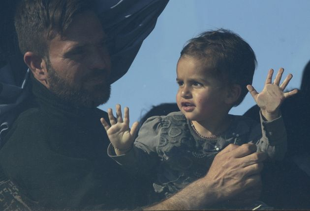 A man and a child are seen through a window of a bus bound for another camp in central Greece. About...