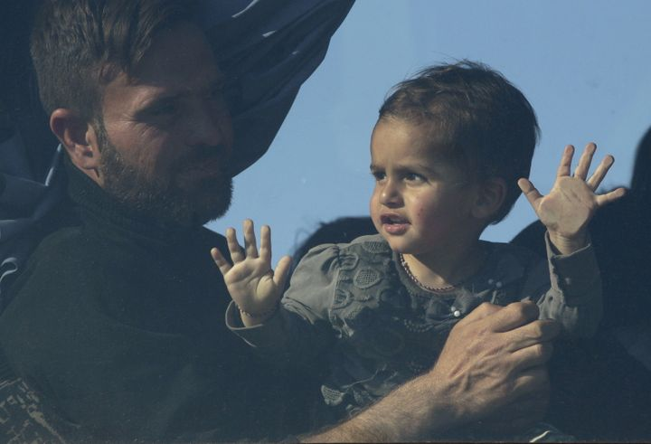 A man and a child are seen through a window of a bus bound for another camp in central Greece. About 12,000 mi