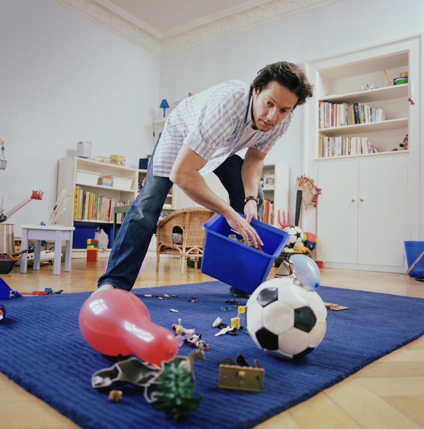 Man in children's bedroom,  placing toys on floor in box