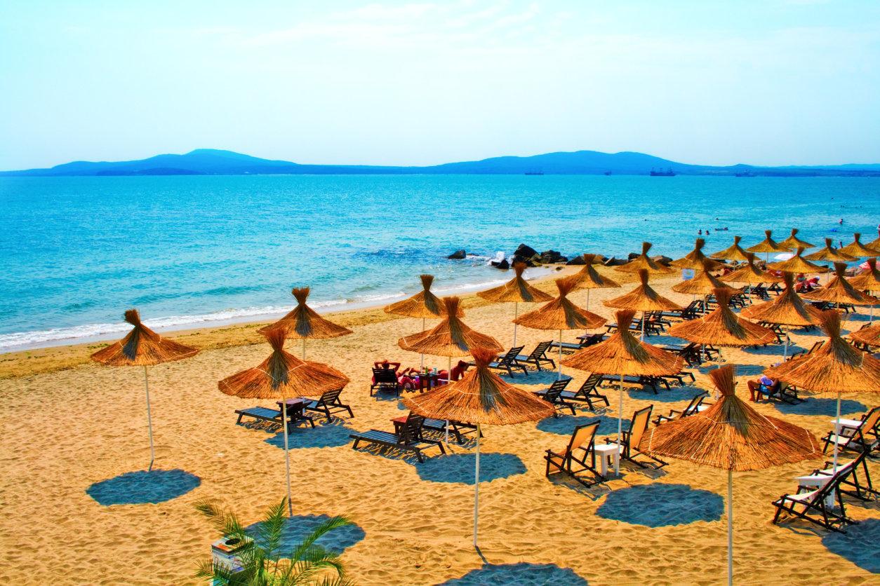 Straw umbrellas on peaceful beach in Bulgaria.
