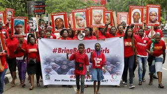 Bring Back Our Girls (BBOG) campaigners hold banners as they walk during a protest procession marking the 500th day since the abduction of girls in Chibok, along a road in Lagos August 27, 2015. The Islamist militant group Boko Haram kidnapped some 270 girls and women from a school in Chibok a year ago. More than 50 eventually escaped, but at least 200 remain in captivity, along with scores of other girls kidnapped before the Chibok girls.     REUTERS/Akintunde Akinleye