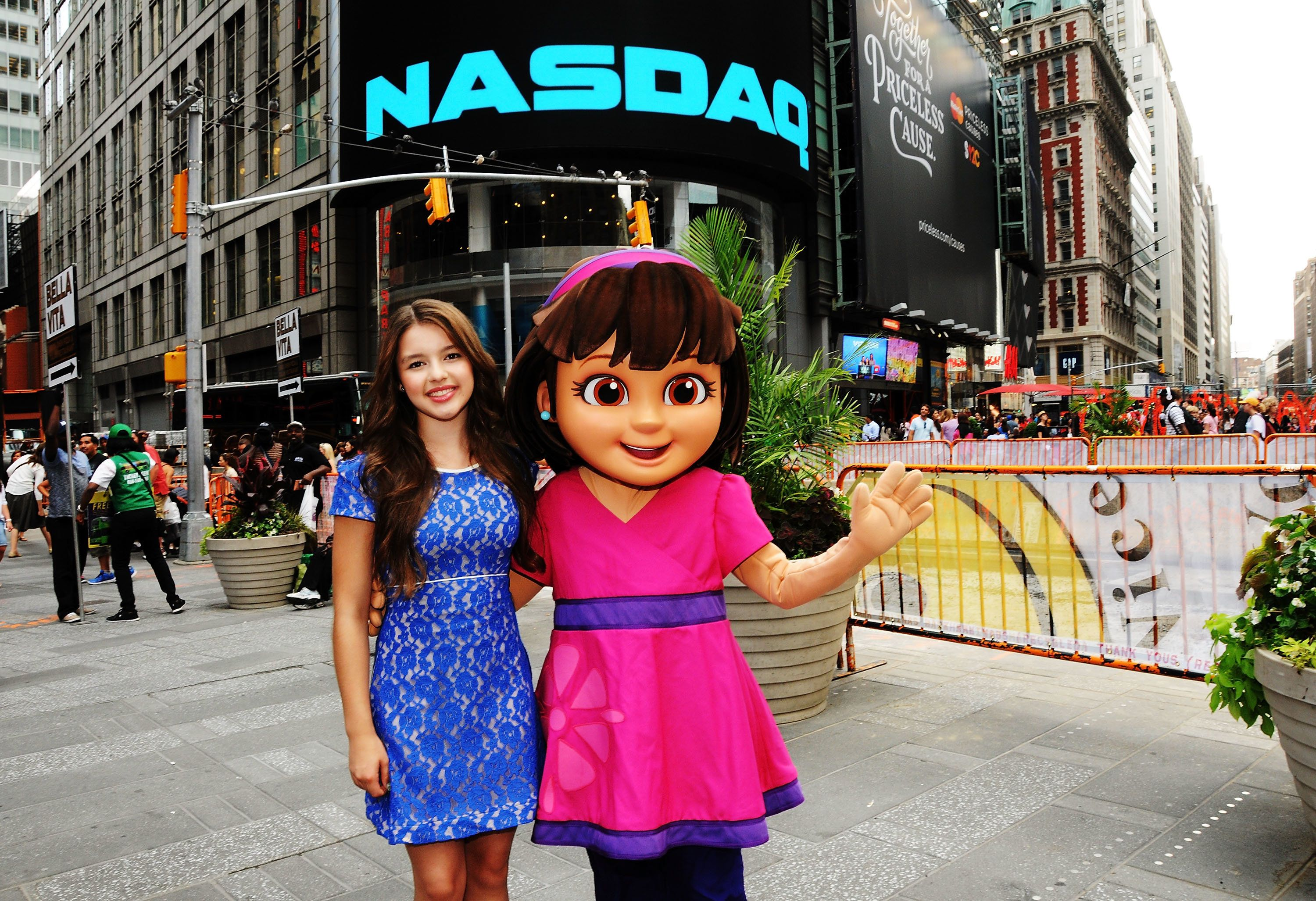 NEW YORK, NY - JULY 29: The voice of 'Dora' in 'Dora and Friends' and 'Dora the Explorer' Fatima Ptacek (L) poses with Nickelodeon's character 'Dora' outside the closing bell at the NASDAQ MarketSite on July 29, 2014 in New York City.  (Photo by Desiree Navarro/WireImage)