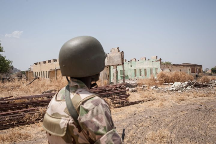 A Nigerian soldier looks at the remains of the Chibok school, where the girls were captured, still in ruins this March. The&n