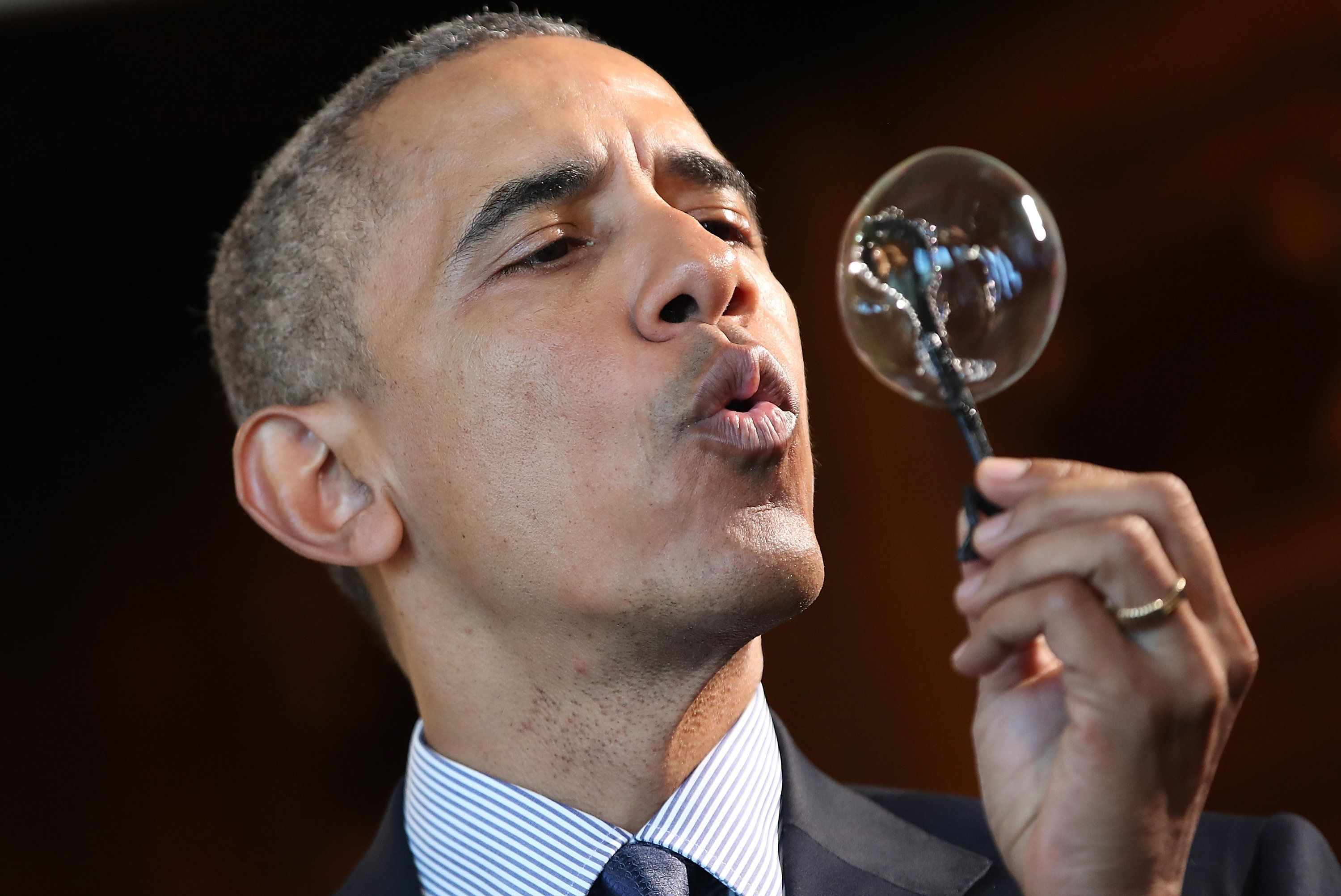 U.S. President Barack Obama blows a bubble from a bubble wand made with a 3D printer by nine-year old Jacob Leggette while to