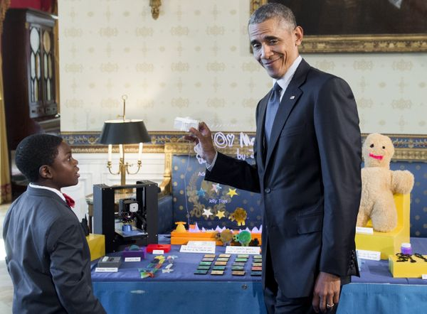 President Barack Obama holds up a copy of the White House that was created using a 3D printer by 9-year-old Jacob Leggette of