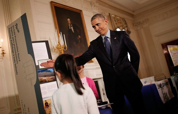 U.S. President Barack Obama listens to sisters Kimberly Yeung (L) and Rebecca Yeung (R) explain their science project while t