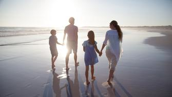 Family walking together on a beach at sunset
